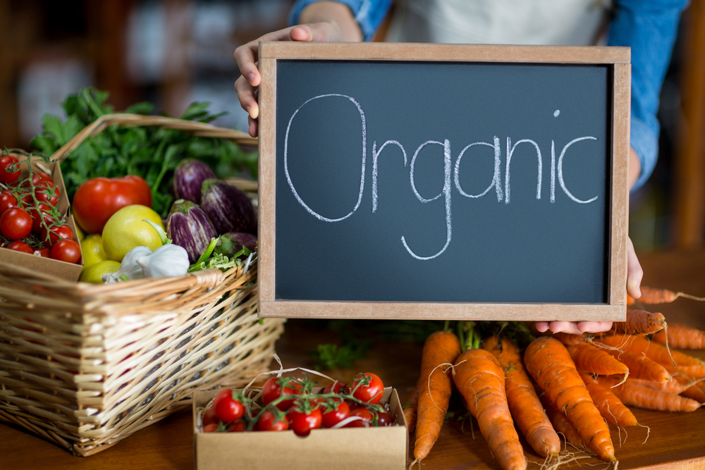 Female staff holding organic sign board in supermarket